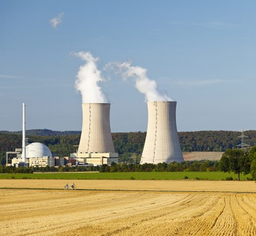 A nuclear power station with hill landscape and blue sky.